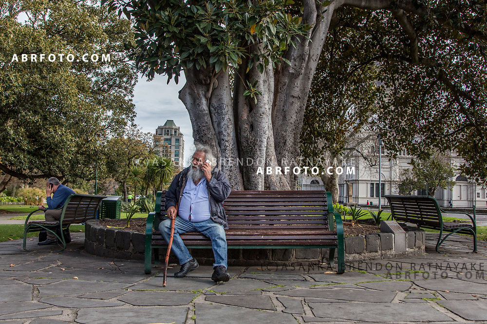 An Aboriginal elder using his phone while sitting under the Moreton Bay Fig tree in Fitzroy, Melbourne, Australia, September 1, 2017. The Moreton Bay Fig tree in the Carlton Gardens was a meeting point for Aboriginal community leaders during the early 1900's where issues of Aboriginal affairs were discussed. Asanka Brendon Ratnayake for the New York Times