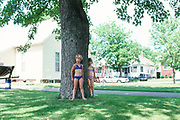 Two young girls in bathsuits leaning on a tree's trunk in Beardstown, Illinois