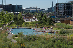 © Licensed to London News Pictures. 19/07/2016. London, UK. Londoners enjoy the cooling waters of King's Cross pond on the hottest day of the year so far, with temperatures expected to reach 35C in the capital.  The UK's first ever man-made fresh water public bathing pond is a piece of innovative Land Art, within a working construction site area of London's King's Cross designed by Ooze architects. Photo credit : Stephen Chung/LNP