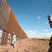 In the desert of Mexico, two foreign exchange students(one from China, one from the Netherlands) take photographs at the border fence built on the Mexico/US boundary near Agua Prieta Mexico and Douglas, Arizona. The newly built fence is part of the project to secure the nearly 2,000 mile border - which is widely considered the most frequently traveled international border in the world, with an estimated 250 legal and 500 million illegal crossings every year. Neither men did not attempt to cross.