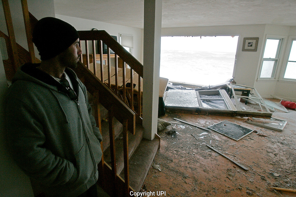 Justin LaCentra looks into the living room of his ocean-front apartment, which was flooded out from a storm surge on Turner Road in Scituate, Massachusetts on December 27, 2010.  The surge was due to a blizzard  which caused coastal flooding and dumped over a foot and a half of snow in other parts of the state.   UPI/Matthew Healey