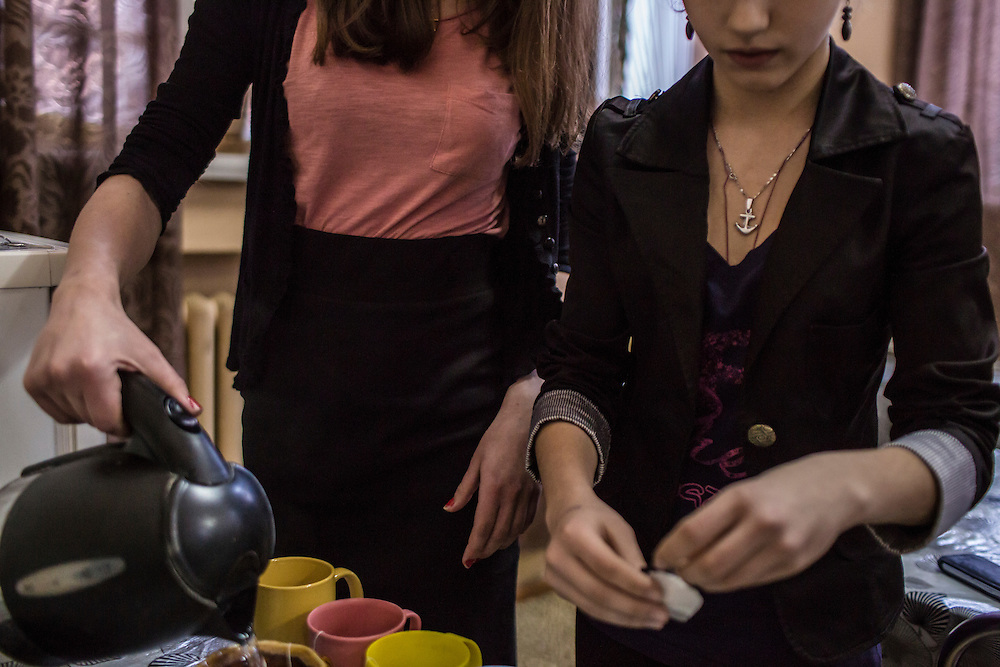 Ielizaveta Tinitskaia, age 16, left, and Karina Varfolomieieva, age 14, pour tea for visiting journalists on Friday, February 12, 2016 in Novgorodske, Ukraine.