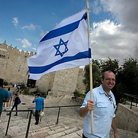 An Israeli man holding an Israeli flag walks outside the Dasmascus gate on Oct. 8, 2015. <br />