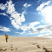 A young boy with a sand board, in Lancelin sand dunes, north of Perth, Australia.