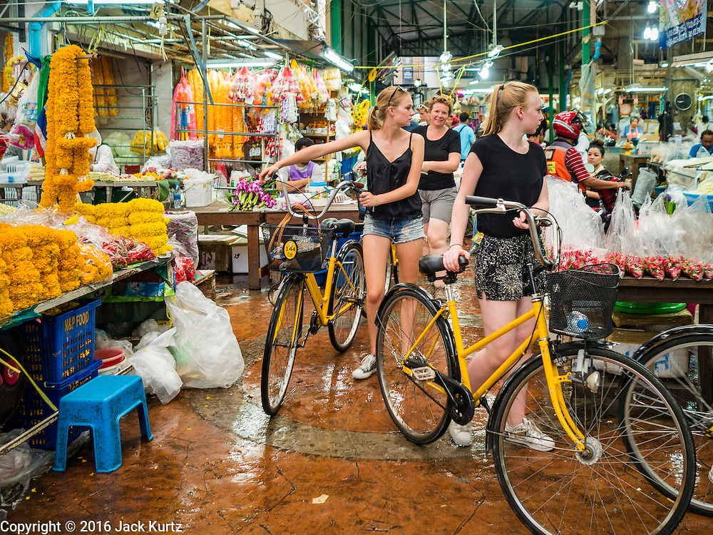 """11 AUGUST 2016 - BANGKOK, THAILAND:       Tourists on a group tour push their bicycles through Pak Khlong Talat in Bangkok. Pak Khlong Talat (literally """"the market at the mouth of the canal"""") is the best known flower market in Thailand. It is the largest flower market in Bangkok. Most of the shop owners in the market sell wholesale to florist shops in Bangkok or to vendors who sell flower garlands, lotus buds and other floral supplies at the entrances to temples throughout Bangkok. There is also a fruit and produce market which specializes in fresh vegetables and fruit on the site. It is one of Bangkok's busiest markets and has become a popular tourist attraction.  PHOTO BY JACK KURTZ"""