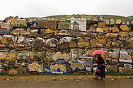 An elderly woman walks by a large mani stone pile near the entrance to a monastery in Litang, Tibet (China).