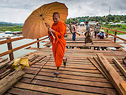 16 SEPTEMBER 2014 - SANGKHLA BURI, KANCHANABURI, THAILAND: A Buddhist monk from the Mon community walks across a repaired section of the Mon Bridge. The 2800 foot long (850 meters) Saphan Mon (Mon Bridge) spans the Song Kalia River. It is reportedly second longest wooden bridge in the world. The bridge was severely damaged during heavy rainfall in July 2013 when its 230 foot middle section  (70 meters) collapsed during flooding. Officially known as Uttamanusorn Bridge, the bridge has been used by people in Sangkhla Buri (also known as Sangkhlaburi) for 20 years. The bridge was was conceived by Luang Pho Uttama, the late abbot of of Wat Wang Wiwekaram, and was built by hand by Mon refugees from Myanmar (then Burma). The wooden bridge is one of the leading tourist attractions in Kanchanaburi province. The loss of the bridge has hurt the economy of the Mon community opposite Sangkhla Buri. The repair has taken far longer than expected. Thai Prime Minister General Prayuth Chan-ocha ordered an engineer unit of the Royal Thai Army to help the local Mon population repair the bridge. Local people said they hope the bridge is repaired by the end November, which is when the tourist season starts.   PHOTO BY JACK KURTZ