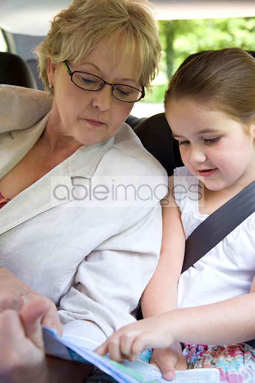 Grandmother reading map with granddaughter inside car