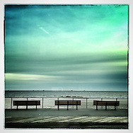 Long Beach, NY: March 2015--- ON a chilly winter day benches along the Long Beach, NY boardwalk don't have many customers. The day has a green cast and the beach looks quiet and empty.