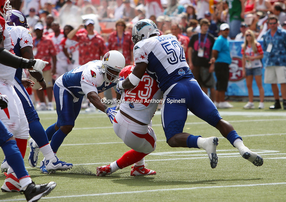 HONOLULU, HI - FEBRUARY 08: AFC All-Stars running back Ronnie Brown #23 of the Miami Dolphins gets gang tackled by linebacker Jon Beason #52 of the Carolina Panthers and strong safety Adrian Wilson #24 of the Arizona Cardinals of the NFC All-Stars in the 2009 NFL Pro Bowl at Aloha Stadium on February 8, 2009 in Honolulu, Hawaii. The NFC defeated the AFC 30-21. ©Paul Anthony Spinelli *** Local Caption *** Ronnie Brown;Jon Beason;Adrian Wilson