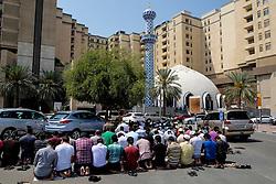 Many men praying on Friday outside mosque at Burjuman shopping centre in Dubai United Arab Emirates