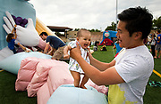 Evelyn Shiu, left, enjoys a bounce with her dad, Kai, on an inflatable character during the 4th annual Yum Yum Fest held at Breese Stevens Field, Sunday, August 6, 2017.