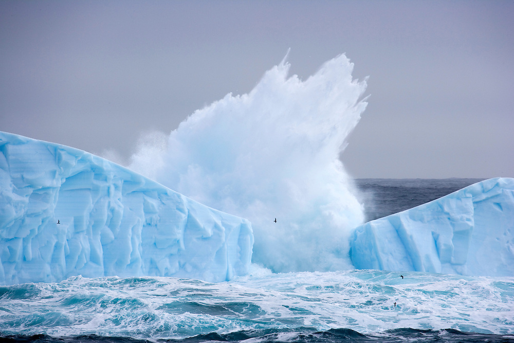 February 6th 2007. Southern Ocean. Birds fly past an iceberg being battered by waves in the Ross Sea.