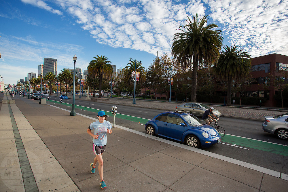 Een vrouw is aan het hardlopen langs de boulevard in San Francisco. Haar blauwe outfit komt overeen met een blauwe Volkswagen Kever die geparkeerd staat. De Amerikaanse stad San Francisco aan de westkust is een van de grootste steden in Amerika en kenmerkt zich door de steile heuvels in de stad.<br /> <br /> A woman runs at the boulevard in San Francisco. Her blue outfit matches the color of the Volkswagen Beetle parked. The US city of San Francisco on the west coast is one of the largest cities in America and is characterized by the steep hills in the city.