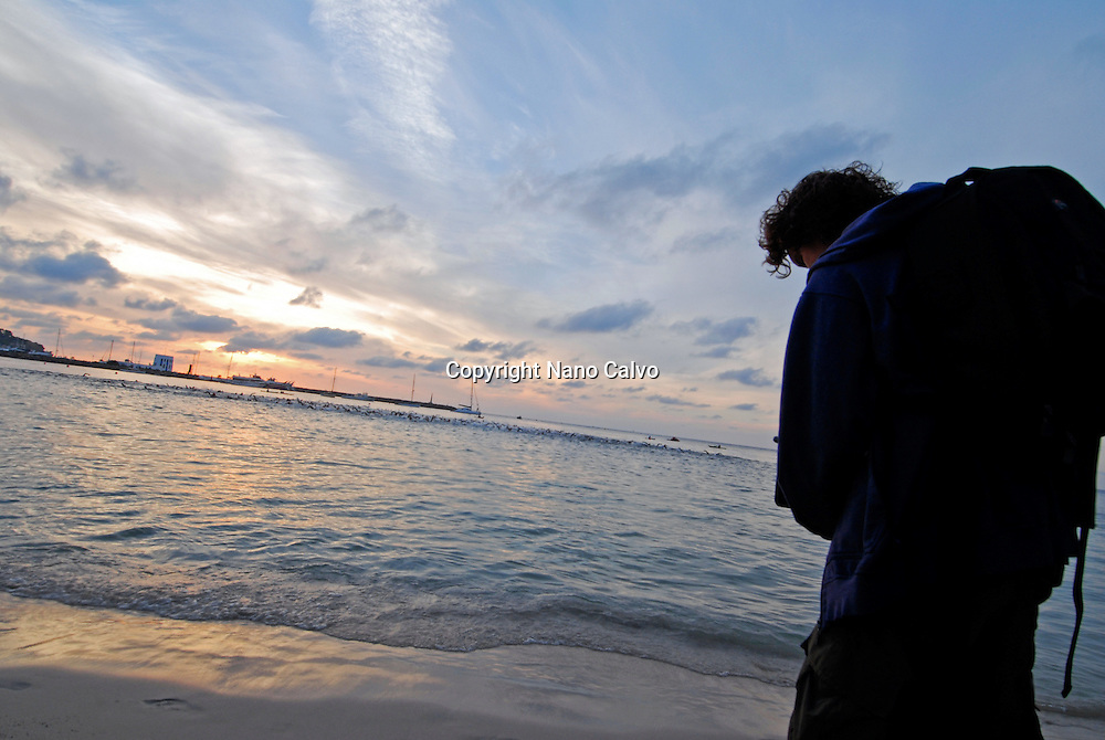 Young man with packpack on the beach, at sunrise