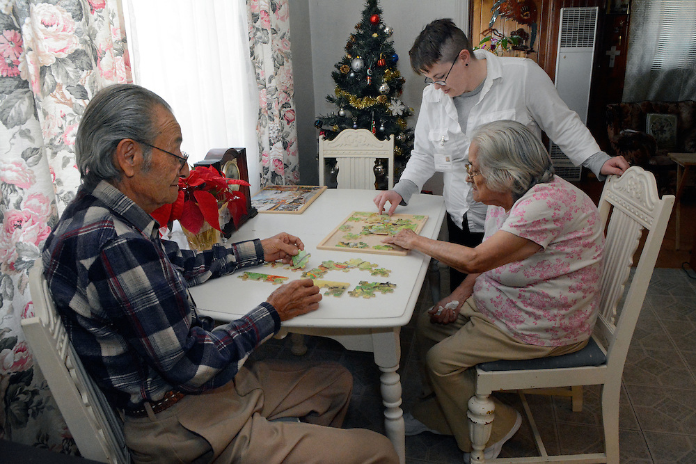jt120916l/biz/jim thompson/  Caregiver Deminica Stout help Henry and Louise Gallegos work on a jigsaw puzzle in their home. Friday Dec. 09, 2016. (Jim Thompson/Albuquerque Journal)