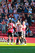 Brentford midfielder Lewis Macleod (4) surrounded by his teammates after heading in Brentford's first in the 40th minute EFL Sky Bet Championship match between Brentford and Nottingham Forest at Griffin Park, London, England on 1 September 2018.