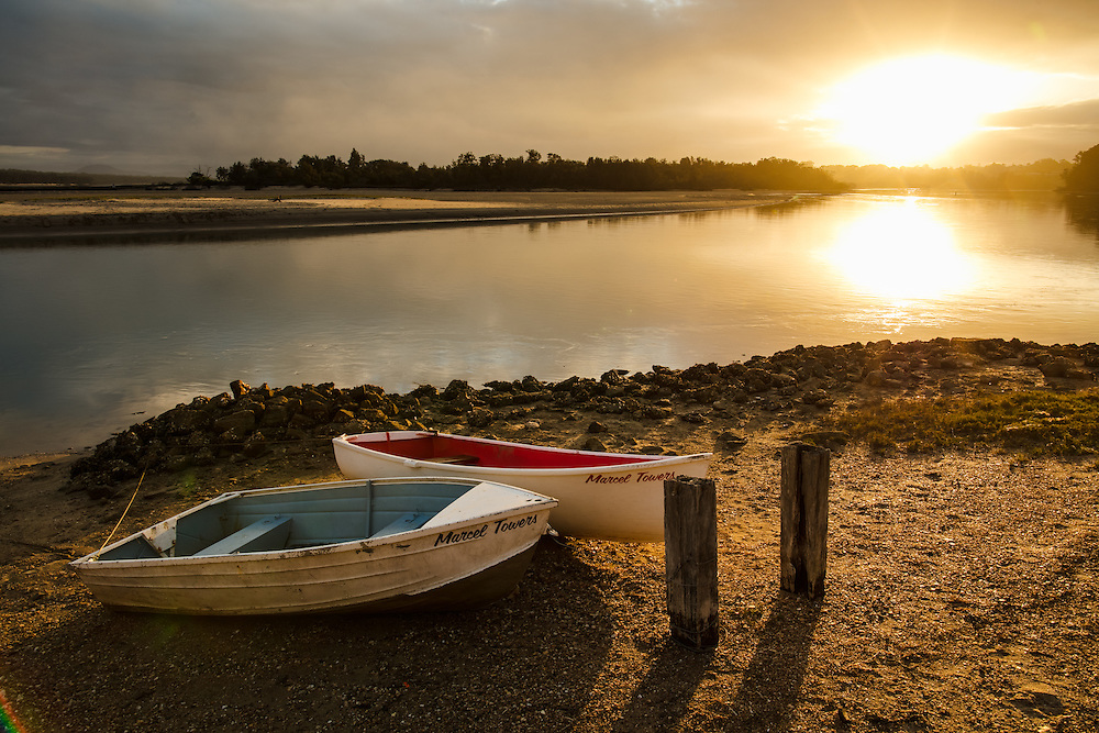 A pair of tied boats lie on the edge of the Nambucca River as the sun sets. Nambucca Heads.