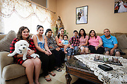 The Marzana family at home in Gilbert, Arizona Aug. 23, 2015. Zinah, third from right, was severely injured and her husband killed in Iraq when they were shot by a motorist from whom they had asked for directions. Seated from left: Sarah, Vian, Hanne, Shams, Mariela (baby), Fadi, Zinah Victoria and Nageeb. (Nancy Wiechec for ONE magazine)