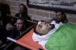 April 14, 2018 - Gaza City, The Gaza Strip, Palestine - Relatives of 28-year-old Palestinian Islam Herzallah, who was shot by Israeli troops east of Gaza City and transported to a hospital where he died, mourns over his body during his funeral in Gaza City on April 14, 2018. Islam's death brings to 34 the number of Palestinians killed in two weeks of protests and clashes along Gaza's border with Israel. (Credit Image: © Mahmoud Issa/Quds Net News via ZUMA Wire)