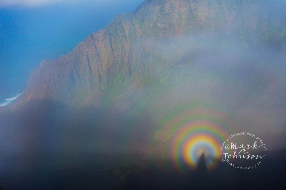 Brocken Spectre (circular rainbow) of person above Kalalau Valley, Na Pali Coast, Kauai, Hawaii