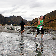 Runner Anna Dungey crosses Moke Creek on the Ben Lomond High Country Station during the Pure South Shotover Moonlight Mountain Marathon and trail runs. Moke Lake, Queenstown, New Zealand. 4th February 2012. Photo Tim Clayton