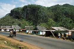 Men riding along the road near Sorao; Cuba; on a cart pulled by a horse; with houses in background,