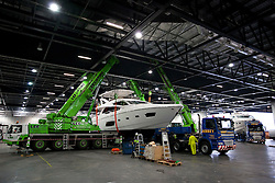 © Licensed to London News Pictures. 22/12/2012. London, UK. A Sunseeker 75 Manhatten luxury yacht is prepared by workers inside the Excel Centre ahead of the Tullett Prebon London Boat Show in London today (22/12/12). The show runs from 12th to the 20th of January 2013. Photo credit: Matt Cetti-Roberts/LNP