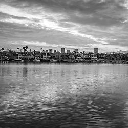 Newport Beach California skyline sunrise black and white photo with Fashion Island office buildings, Balboa Island homes, and Newport Harbor. Newport Beach is an affluent beach city in Orange County Southern California.  Photo is high resolution. Copyright ⓒ 2017 Paul Velgos with All Rights Reserved.