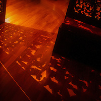 Sunlight shining through a carved wooden panel.