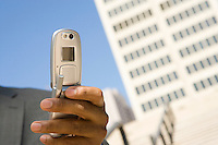 Close-up of businessman's hand with mobile phone, outdoors