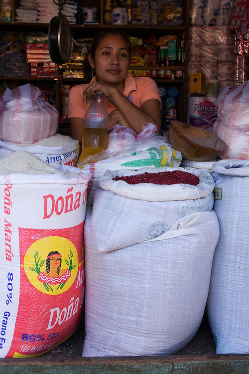 A woman rests behind sacks of Rice and red Beans with many other goods for sale behind her. Granada, Nicaragua