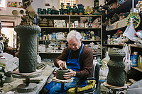 SCIACCA, ITALY - 22 APRIL 2015: SCIACCA (AG), ITALIA - 22 APRILE 2015: Ceramic artist Gaspare Patti (78), makes a ceramic pot in his workshop in Sciacca, Italy, on April 22nd 2015.<br /> <br /> Gaspare Patti, a ceramic maestro since 1954, has his worhsop in front of the Chiesa Madre of Sciacca, a city that has a long-standing tradition of ceramic production.<br /> <br /> Gaspare Patti prides himself on his idiosyncratic style and his shop is packed with strange and original creations.<br /> <br /> ###<br /> <br /> Giulio Lorubbio (66 anni), detto Lulù, posa per un ritratto all'ingresso della sua abitazione nel Cortile Carini a Sciacca il 22 aprile 2015. Giulio Lorubbio è un artista autodidatta e istintuale che crea mosaici e collage tridimensionali con elementi riciclati trovati per strada, in spiaggia, in campagna: frammenti di vetro, pezzi di legno, reti, conchiglie, piastrelle rotte.