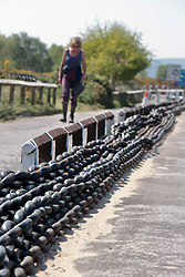 Covid 19 - Redundant chains laid out on the approach road that were used to haul the the Shell Bay to Sandbanks Chain Ferry. A vital service to key workers traveling to Poole/Bournemouth/Christchurch from the Isle of Purbeck Dorset, withdrawn from service for lack of business owing to coronavirus, causing a 22 mile detour. UK April 2020. MR
