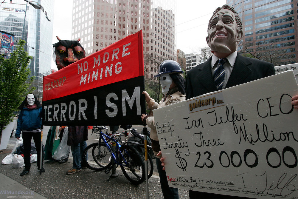 "Anti-mining protesters setup outside the offices where Goldcorp's annual general meeting is taking place with a sign that reads: ""Goldcorp: No more mining terrorism!"". A protester with a mask emulates Chief Executive Officer Ian Telfer who claimed 2006 earning of 23 million Canadian dollars despite uproar from Goldcorp affected communities in Central America. Vancouver, Canada. May 2nd, 2007."