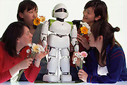 "Fans invited off a street in Tokyo's Harajuku area to meet Pino pose with the popular robot. Pino, short for Pinocchio (after the fabled wooden puppet that becomes a human boy), is a full-bodied, child-sized, humanoid robot. Even before it demonstrates the ability of a wide range of bipedal movements it already has a national following in Japan after the release of a music video called ""Can You Keep a Secret"" in which the robot stars alongside one of Japan's most popular recording artists, Hikaru Utada. It has elevated Tatsuya Matsui, the artist who created the robot design, to celebrity status and provoked murmurs of dissent by some in the robotics community who see the robot as a commercial entity rather than a serious research project. Interestingly, the robot project is part of a large ERATO grant from the Japan Science and Technology Corporation, a branch of the Science and Technology Agency of the Japanese government. Project creator Hiraoki Kitano  believes that the aesthetics of a robot are important in order for it to be accepted by humans into their living space. At the Kitano Symbiotic Systems, Tokyo, Japan."