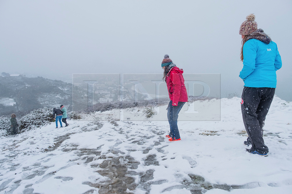 © Licensed to London News Pictures. 10/12/2017. Aberystwyth, UK. People enjoy the view of the first snow of the winter at Aberystwyth on the Welsh coast, as the wintry conditions spread of much of the middle of the UK.  People are out  walking on Constitution Hill overlooking the town, making the most of the snowy scenes .Photo credit: Keith Morris/LNP