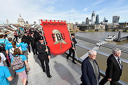 © Licensed to London News Pictures. 13/10/2018. LONDON, UK.  After a formal wreath-laying ceremony at the National Firefighters' Memorial next to St Paul's Cathedral, in memory of fallen firefighters representing every fire service in the UK, members of the Fire Brigades Union (FBU) take part in a formal procession across the Millennium Bridge followed by a service at Southwark Cathedral to commemorate the centenary of the formation of the FBU. The activities are the largest ever ceremonial event for firefighters killed in the line of duty.  Photo credit: Stephen Chung/LNP