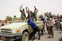 59722704 .Soldiers wave to residents after returning from battlefield, in El Rahad of Sudan's North Kordofan State May 28, 2013. Sudanese army announced on Monday that it has liberated the strategic area of Abu Karshula in South Kordofan State from rebels of the Revolutionary Front. May 28, 2013..UK ONLY