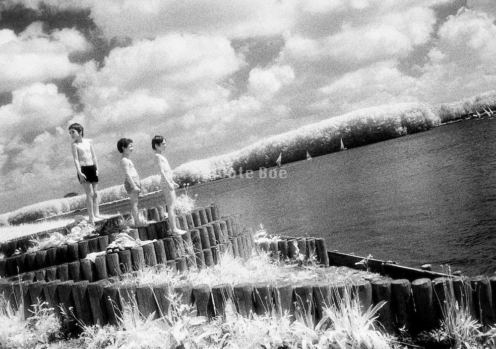 Three boys standing on a dock Holland