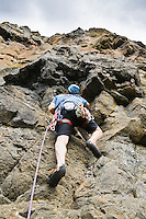 A male rock climber making his way up a steep rock wall.  Lava Point, Tieton River Climbing, Cascade Mountain, Washington, USA.
