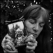 Heather Hafliegh, outside her home in Berkeley on July 10, 2006, closes her eyes as she holds a picture of her niece, Mandy, who committed suicide...Hafliegh was one of thousands of Bay Area Residents who participated in the American Foundation for Suicide Prevention annual  fundraising walk, Out of the Darkness, in San Francisco, CA on July 22, 2006...Photo by Erin Lubin.