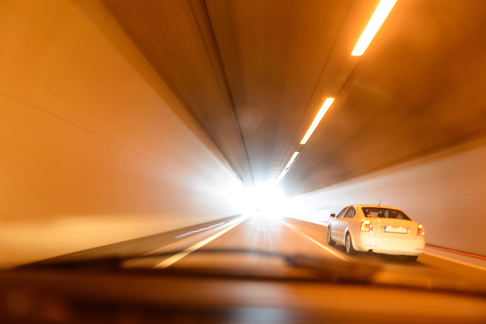 Driving through a tunnel at speed shot through the windscreen from the drivers point of view with motion blur.