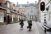 In Utrecht rijden fietsers voorbij een verkeerslicht in de Lange Nieuwstraat. Sinds kort kunnen fietsers vanaf dat punt doorrijden tot een eigen verkeerslicht verderop.<br /> <br /> In Utrecht cyclists past a traffic light at the Lange Nieuwstraat. While cars have to wait, cyclists can pass to the special light a few meters behind/