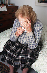 Portrait of elderly woman sitting on bed crying,