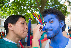 London, July 8th 2017. Thousands of LGBT+ revellers take part in the annual Pride in London parade under the banner #LoveHappensHere. PICTURED: A man gets blue body paint applied to his face.