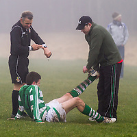Rhine Rover's Graham O'Connor receives treatment from the manager Rory O'Connor while reminded of the time by match referee Terry Kennedy