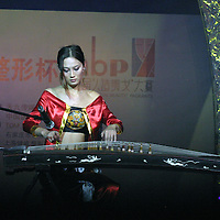 "BEIJING, 18 DECEMBER 2004: Cheng Lili,22, a participant  performs at  the ""first worldwide artificial beauty pageant "" ,shows her musical skills  in a theatre in Beijing, 18 December , 2003, in China...Beauty business in China , from cosmetic surgeries to hair brush sales, has amounted to more than USD 7 billion in 2003. The contest for women who have undetgone plastic surgery was organized after Yang Yuan, a young would-be model, was disqualified earlier on this year when organizers discovered that she'd had plastic surgery. Yang was present during the contest to introduce her biography that explains why she has the right to ""improve"" her natural features..."