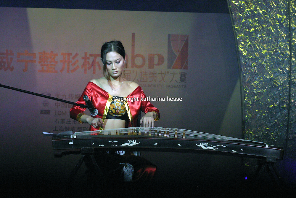 """BEIJING, 18 DECEMBER 2004: Cheng Lili,22, a participant  performs at  the """"first worldwide artificial beauty pageant """" ,shows her musical skills  in a theatre in Beijing, 18 December , 2003, in China...Beauty business in China , from cosmetic surgeries to hair brush sales, has amounted to more than USD 7 billion in 2003. The contest for women who have undetgone plastic surgery was organized after Yang Yuan, a young would-be model, was disqualified earlier on this year when organizers discovered that she'd had plastic surgery. Yang was present during the contest to introduce her biography that explains why she has the right to """"improve"""" her natural features..."""
