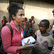 Journalist Mariane Pearl and Dr. Julian Atim talk with children in the town of Kyengera.